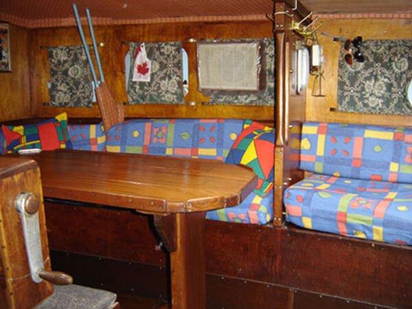 Спальные места и стол в кают-компании яхты Риф